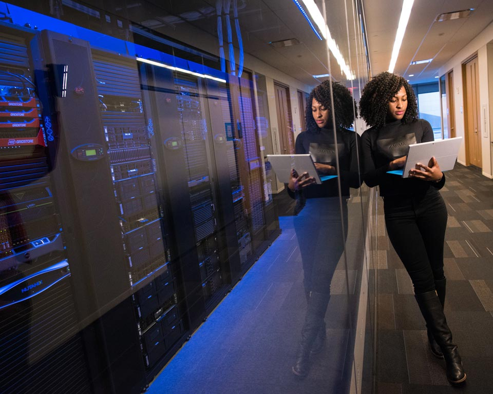 Woman with laptop in front of servers